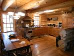 Spacious 3 story log home with open floor plan features colonial style kitchen