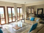 Living room opens onto spacious veranda with 3 sets of double doors and panoramic sea views