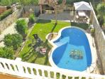 view from the balcony to the pool and the garden