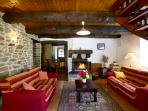Living area with wood burning stove, set beneath the beams