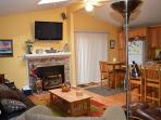 Living room with a flat screen satellite TV/VCR/5-Disc DVD player with surround sound and a gas fireplace