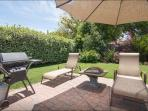 Relaxing patio with BBQ grill, lounge chairs and sun umbrella