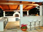 The outdoor kitchen has 2 fridges,pizza oven, BBQ, gas stove, kettle, toaster, juicer & the bar area