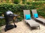 Quiet back patio with charcoal grill.