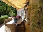 espace repas storisé sur la terrasse, face à la piscine