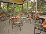 Screened porch has a high ceiling with a great fan for a relaxing evening.