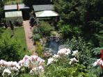 Blick in den Garten auf Teich, Terasse und Blockhaus