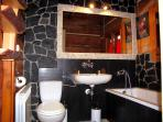 Bathroom with comfortable bath surrounded by natural Tatra and Balinese stone and wood.