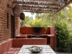 Outdoor BBQ with outdoor dining table, and storage room on the left