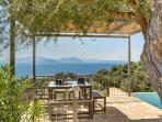 Shaded outdoor table beside the swimming pool with stunning sea view
