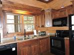 Kitchen view with window overlooking river, stove, microwave, fridge, and DW
