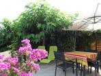 terrasse avec transats, table et chaises et plancha gaz