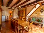 Gorgeous formal dining area with wood burning stove, lovely stone walls, and beautiful tile floors