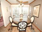 Dining area with panoramic view and seating for 6 plus 4 at kitchen counter.