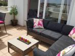 Balcony with lounging and dining furniture.