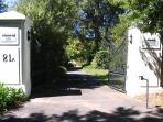 Entrance gates leading onto treed driveway and parking area
