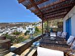 A big dining table on the porch and panoramic view of the village and the Aegean Sea.
