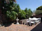 The braai area and leafy plants, together with a dog water feature in the outside entertainment area