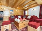 The living area has a large l-shaped sofa, and plenty of additional comfortable seating