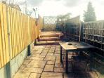 Private garden with BBQ and a raised patio area.