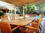 Teak outdoor table seats 8 to 10.   There's another round teak table in background that seats 4 to 6