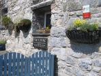Spring.  Entrance gate. Parking to  the side of the cottage.Registered Four Star with Visit Wales