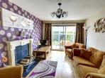 The comfortable sitting room has sliding patio doors leading into the dining conservatory