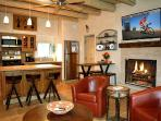 Great room with large flat screen TV, upscale contemporary kitchen