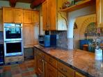 Wine/beverage cooler to left of double built in oven + pass through window between kitchen & dining for ease of serving
