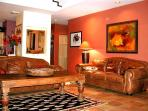 Ample seating with dual leather sofas & charis, upscale furnishings & art