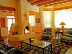 Kiva fireplace, bay windows show off spectacular Taos mountain views