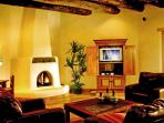 Spacious Living Room showing Kiva Fireplace & Viga Ceilings and armoir with Satellite TV