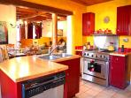 Stainless gourmet oven / range, butcher block counters, red enamel cabinets all create extreme southwest ambiance