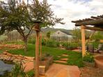 View past vegetable garden and pond to green house and more mountains