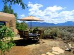Outdoor dining or gathering spot with umbrella & mountain views