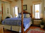 Queen guest bedroom with wood burning kiva fireplace
