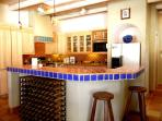 Island kitchen showing ample wine rack & stools for two chef''s helpers