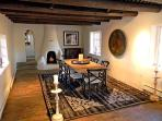 Large sunken dining room, kiva fireplace, step up through traditional narrow arched door way to 3 bedroom area
