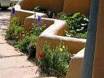 Flower garden flanking stairway to studio deck