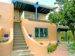 Custom designed, graceful adobe wall stairwell to covered panoramic view deck and studio