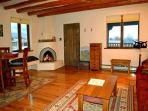 Warm glow from 'candles only' kiva fireplace and showing 2 of 3 panoramic view windows