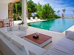The pool lounge with its white cushioned sofas and low slung table