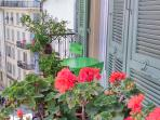 Très long balcon fleuri avec table et chaises surplombant le square
