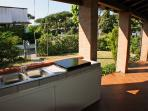 Ampio patio angolare arredato con mobili da esterno e cucina