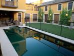 Coqueto jardín con piscina y barra de bar.