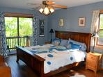 'Reve Parisien' bedroom featuring king bed, attached bathroom, vanity and deck.