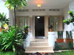 View from the front: colonial styled house with lots of opening and big garden