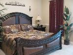 Master bedroom with king bed and door to balcony overlooking the pool. Peek-a-boo view of the ocean.