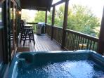 Enjoy the charcoal grill, hot tub and sitting area on private deck