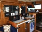 Galley with microwave toaster, coffee maker and fridge.